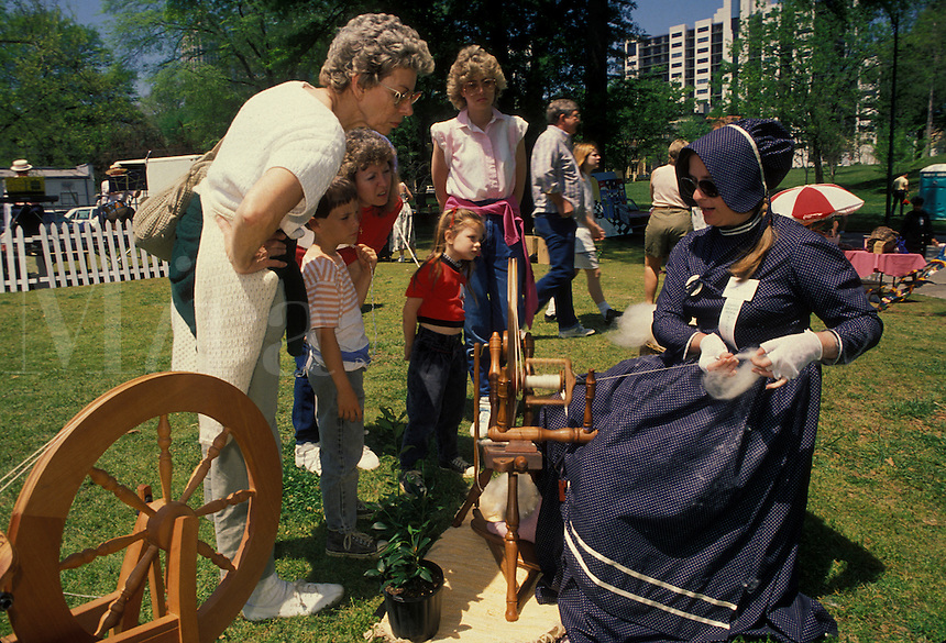 AJ1820, spinning wheel, artisan, antique, demonstration, wool. Georgia. A woman spins yarn from wool on a spinning wheel as people watch at the Dogwood Festival in Piedmont Park in Atlanta, Georgia.
