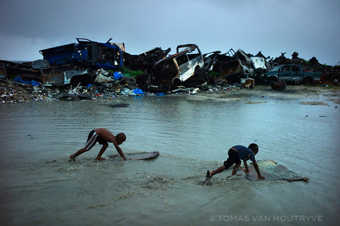 Children skim the water on makeshift surf boards near a pile of wrecked cars on Ebeye island, Kwajalein Atoll on June 18, 2012. The tiny overcrowded island is cluttered, with trash, junk and discarded military surplus items from the neighboring U.S. Army base.