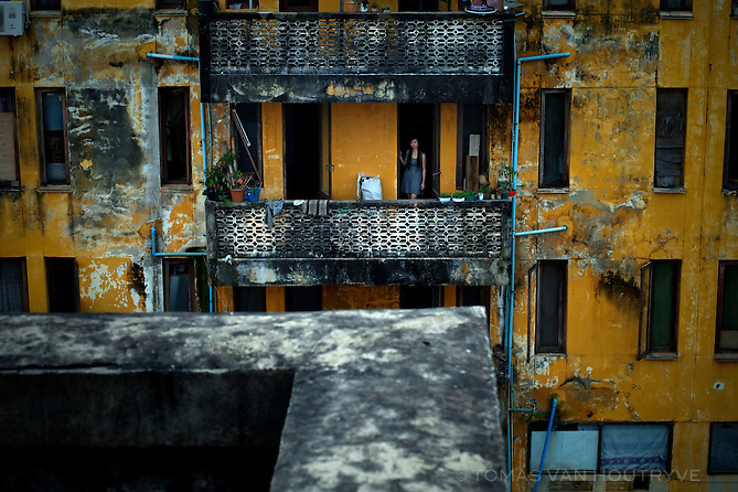 A woman stands on a balcony of a building constructed by Soviet architects in 1985 in Vientiane, Laos on March 27, 2011.