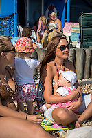 """A young woman breastfeeding her baby while sunbathing on the beach with a friend. The baby is feeding while sitting on its mother's lap.<br /> Image from the breastfeeding collection of the """"We Do It In Public"""" documentary photography picture library project: <br />  www.breastfeedinginpublic.co.uk<br /> <br /> <br /> Hampshire, England, UK<br /> 03 /09/2013<br /> <br /> © Paul Carter / wdiip.co.uk"""