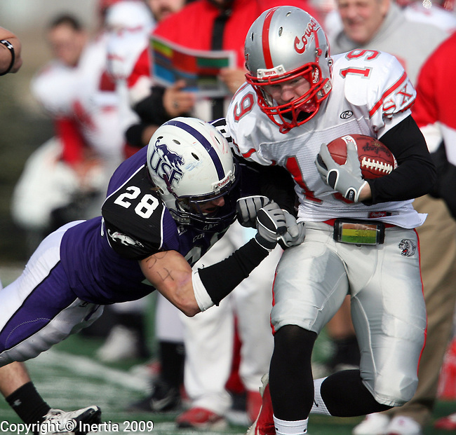 SIOUX FALLS, SD - DECEMBER 5:  Wes Gastel #19 of the University of St. Xavier is pushed out of bounds by Trevor Holleman #28 of the University of Sioux Falls in the first quarter of their NAIA semifinal game Saturday afternoon at the USF Complex in Sioux Falls. (Photo by Dave Eggen/Inertia)