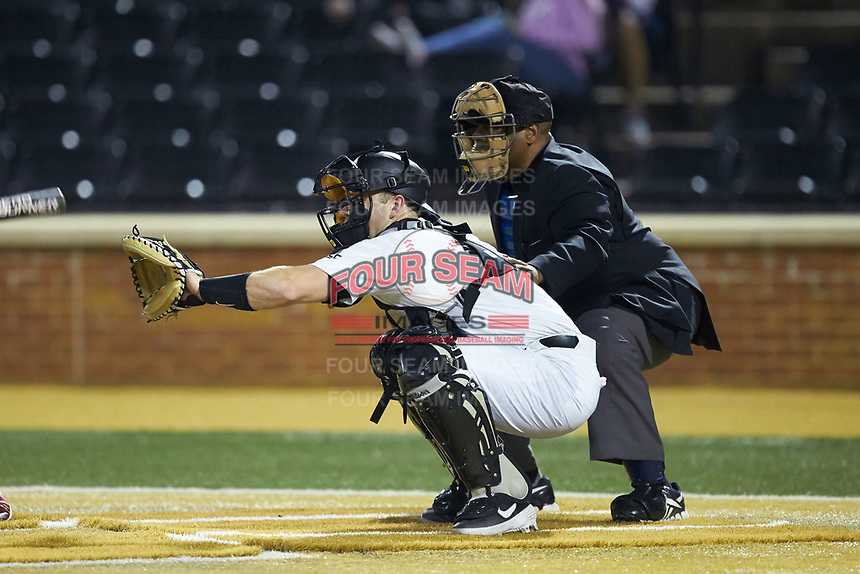 Wake Forest Demon Deacons catcher Brendan Tinsman (9) sets a target as home plate umpire Gregory Street looks on during the game against the Sacred Heart Pioneers at David F. Couch Ballpark on February 15, 2019 in  Winston-Salem, North Carolina.  The Demon Deacons defeated the Pioneers 14-1. (Brian Westerholt/Four Seam Images)
