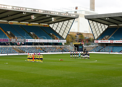 31st October 2020; The Den, Bermondsey, London, England; English Championship Football, Millwall Football Club versus Huddersfield Town; Millwall and Huddersfield Town starting eleven players stand while a member of the Armed Forces playing the bugle before kick off for Remembrance Sunday on the 11th November
