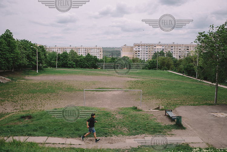 A child runs past a football pitch in the Ciocana district.