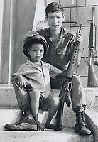 1973 FILE PHOTO -<br /> <br /> Stranger in a strange land: Children those homes were destroyed just before ceasefire lock around their first foreign visitor; Star reporter Jack Cahill. The village of An-My is on Route 13 north of Saigon. The most popular people with the children however; are the South Vietnamese soldiers who are still posted in many towns and villages to ensure the enemy does not try to regain control of the areas. Soldier disarmed his weapon before playing with boy.