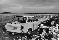 GERMANY in 1990, former East Germany, German Democratic Republic GDR, typical plastic car Trabant with fascist Nazi symbol swastika Hakenkreuz on wild dumping site in village Plauerhagen, Mecklenburg, black and white image with film grain