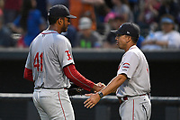 Pitcher Denyi Reyes (41) of the Greenville Drive is congratulated by manager Iggy Suarez after using just 92 pitches to post a nine-inning complete-game shutout against the Columbia Fireflies on Sunday, May 27, 2018, at Spirit Communications Park in Columbia, South Carolina. Greenville won, 3-0. It was the first complete-game shutout in the South Atlantic League this season.(Tom Priddy/Four Seam Images)