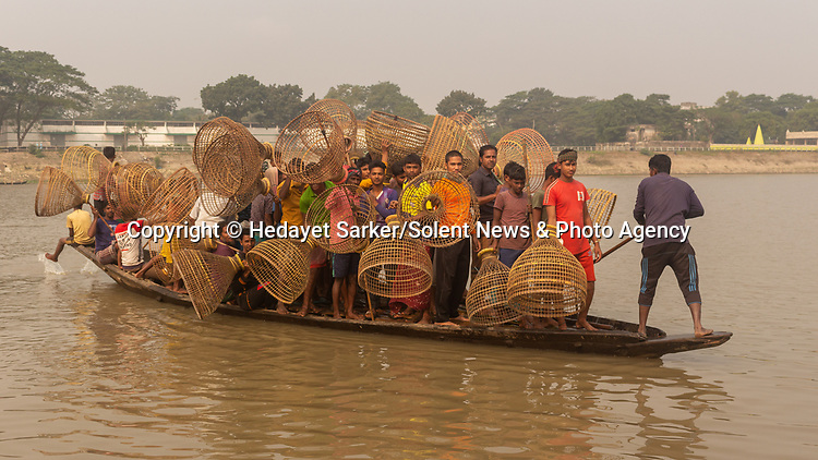 Don't rock the boat.......Dozens of passengers cram onto a crowded boat on their way to a fishing festival.  The fishermen carry polo fishing baskets, made from bamboo.<br /> <br /> The bi-annual Polo Bawa festival involves 150 to 200 people, and the fishermen sing songs together while they fish.  It occurs in the Brahmanbaria district of Bangladesh, where these photos were taken by Mohammad Hedayet Sarker.  SEE OUR COPY FOR DETAILS.<br /> <br /> Please byline: Hedayet Sarker/Solent News<br /> <br /> © Hedayet Sarker/Solent News & Photo Agency<br /> UK +44 (0) 2380 458800
