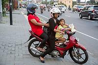 Yogyakarta, Java, Indonesia.  Two Women and Little Girl on Motorbike  about to Enter Evening Traffic, Jl. Laksda Adisucipto Street.