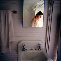 Woman's reflection in bathroom cabinet mirror