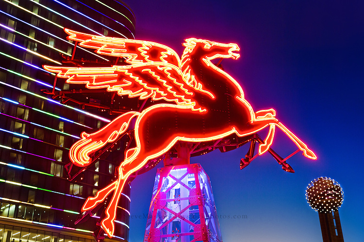 """""""Pegasus - Dallas, Texas"""" - Pegasus, the 'Flying Red Horse', was built atop the Renaissance Revival Magnolia Building (now known at the Magnolia Hotel), by Texlite for the Magnolia Oil Company in 1934. Standing majestically at 450 feet above ground level, the Dallas icon was visible 75 miles away on a clear night. Pilots reported catching sight of it 60 miles south of Hillsboro, and some claimed to see it from as far away as Waco. By 1974, the landmark had experienced structural and weathering issues, and in 1999 a crane and helicopter aided in the removal of the two original forty foot horses. For the city's Y2K Millennium Celebration, the original horses were used as templates to create a brand new winged horses, with the new horses lit high above the Magnolia. The original 1934 winged horses were renovated by Omni Dallas developer Matthews Southwest and set atop a 22 foot oil derrick. Illuminated and mounted, the original Pegasus (pictured) can be viewed in all its glory outside of the magnificent Magnolia Hotel in downtown Dallas."""