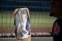 A Salt River Rafters player holds an oar with a photo of hitting coach Shelley Duncan (18), of the Arizona Diamondbacks organization, during an Arizona Fall League game against the Glendale Desert Dogs at Salt River Fields at Talking Stick on October 31, 2018 in Scottsdale, Arizona. Glendale defeated Salt River 12-6 in extra innings. (Zachary Lucy/Four Seam Images)