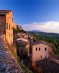 Tuscany, Itlay<br /> Tiled roofs of Montepulciano with farms, green fields and vineyards in the valley below