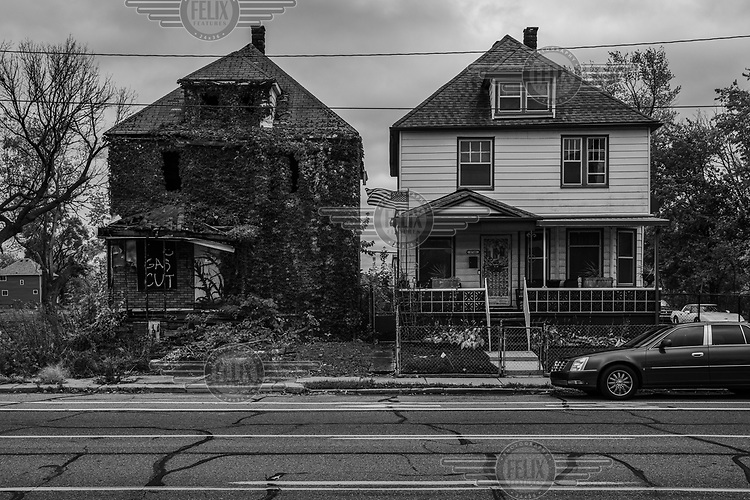 An abandoned and decaying house stands beside one in good repair..