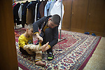 16/11/14. Alqosh, Iraq. Wassam helps Kevin put on a pair of trousers in the room where the orphans keep their clothes.