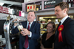 © Joel Goodman - 07973 332324 . 11/04/2015 . Bury , UK . Labour Shadow Chancellor ED BALLS (l) pours a pint . Ed Balls and James Frith (r) , Labour candidate for Bury North , at a campaign stop with the owner of Barista coffee shop (c) at The Rock , Bury in Greater Manchester , UK . The pair met parents and discussed family finances . Photo credit : Joel Goodman
