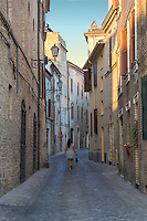 Young Lady walking in the streets of Offida, Italy.