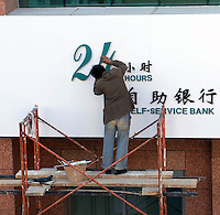 A man adds a sign for 24-hour banking at the Agricultural Bank of China, in Kunming, Yunnan Province.  As China's bank reform and modenize 24-hr banking is one amany services that are being offered to the increasingly wealthy public..