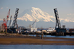 Mount Rainier rises pristine behing the defunct Hylebos Waterway Bridge in Commencement Bay.  The bridge became a victim of progress as ever larger ships began to regularly collide with and damage the structure.  Commencement Bay's history of industry and shipping has led it to designation as the Commencement Bay Nearshore/Tidflats Superfund Site..