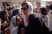 Larkana, Pakistan<br /> November 16, 1988<br /> <br /> Benazir Bhutto is surrounded by admiring Pakistani women as she arrives at a voting station in Larkana.<br /> <br /> Benazir Bhutto is the eldest child of former Pakistan President and Prime Minister Zulfikar Ali Bhutto. She found herself placed under house arrest in the wake of her father's imprisonment and subsequent execution in 1979. In 1984 she became the leader in exile of the Pakistan Peoples Party (PPP), her father's party, though she was unable to make her political presence felt in Pakistan until after the death of General Muhammad Zia-ul-Haq. <br /> <br /> On 16 November 1988 Benazir's PPP won the largest bloc of seats in the National Assembly. Bhutto was sworn in as Prime Minister in December, at age 35 she became the first woman to head the government of a Muslim-majority state in modern times. <br /> <br /> She was removed from office 20 months later under orders of then-president Ghulam Ishaq Khan for alleged corruption. Bhutto was re-elected in 1993 but was again removed by President Farooq Leghari in 1996, on similar charges. Bhutto went into self-imposed exile in Dubai in 1998, until she returned to Pakistan on October 2007, after General Musharraf granted her amnesty and all corruption charges withdrawn.
