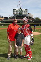 Hall of Fame Chicago Cubs pitcher Ferguson Jenkins poses for a photo with catcher Brian Navarreto #7 and a fan that Jenkins had throw out the first pitch before the Under Armour All-American Game powered by Baseball Factory at Wrigley Field on August 18, 2012 in Chicago, Illinois.  (Mike Janes/Four Seam Images)