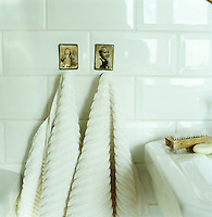 Vintage photographs add character to the pristine white tiled bathroom