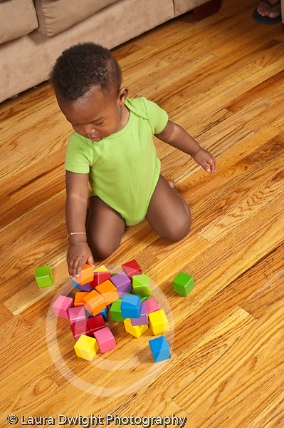 12 month old baby boy kneeling on floor stacking two blocks