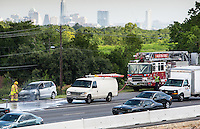 The Austin Fire Department extinguishes a car fire on Texas Loop 1 north MoPac Expressway during afternoon rush-hour traffic with the downtown Austin Skyline in the background.<br />