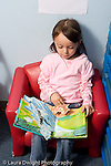Education Preschool 4-5 year olds girl sitting in chair looking at picture book vertical