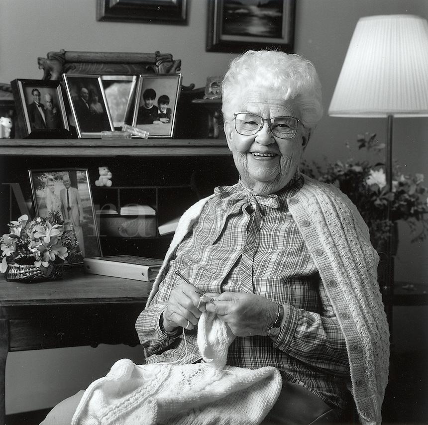 Black and white portrait of female senior citizen, knitting in environment.