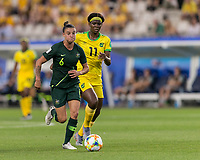 GRENOBLE, FRANCE - JUNE 18: Chloe Logarzo #6 of the Australian National Team dribbles at midfield as Khadija Shaw #11 of the Jamaican National Team pressures during a game between Jamaica and Australia at Stade des Alpes on June 18, 2019 in Grenoble, France.
