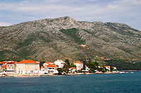 A view over the village and the massive mountains on the peninsula with undulating pattern. Mount Sveti Ilija mountain. Orebic town, holiday resort on the south coast of the Peljesac peninsula. Orebic town. Peljesac peninsula. Dalmatian Coast, Croatia, Europe.