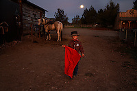 """Ready for action with his red cape, sheriff's badge and mustang Paiute, a young boy stands under the full moon at the Lauman ranch.  Tanner Lauman has won many awards riding his mustang.<br /> <br /> Kitty Lauman (his mother)trains mustangs--as she says working with the horses, not against them.  They have a ranch in Prineville, OR.<br /> <br /> Kitty, her husband Rick and their children, Josie, 2 ½,  and Tanner, 5,  ride mustangs. Kitty Lauman started her career as a horse trainer at the tender age of nine, under the guidance of her grandfather, John Sharp. <br /> <br /> She later became a top Pee Wee and High School Rodeo contestant, competing in barrel racing and cutting, among other events. Despite her mother's assertion that """"horse training isn't a real job,"""" Kitty managed to make a living as a trainer after high school (and her mom now helps out with the business!) <br /> <br /> Kitty won the title of Miss Rodeo Oregon in 1994, and since then, has continued to expand her horse training knowledge and experience.  She placed second in the Extreme Mustang Makeover, a national competition in 2008."""