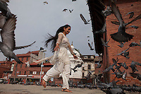 A Nepali young woman plays with pigeons at Pashupatinath Temple in Kathmandu in Nepal.