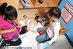 Education preschool 3-4 year olds two girls using medical kit on doll pretend play playing separately horizontal