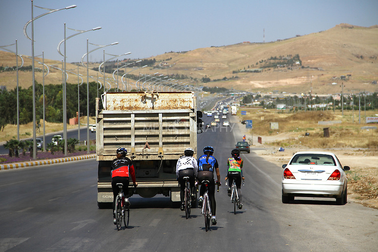 SULAIMANIYAH, IRAQ: Cyclists from the Newroz Club on a road in Sulaimaniyah during a training session.<br /> <br /> Nyan Yassin, 24, is a professional competitive cyclist in Sulaimaniyah in the semi-autonomous region of Iraqi Kurdistan.  She is the captain of an all-female club called Newroz Club, which is the only cycling club for women in Sulaimaniyah, although there are other clubs around Iraq.  She trains and competes on roads that are badly surfaced and busy with traffic.<br /> <br /> Nyan was the first woman to start cycling in Sulaimaniyah.  She was always competitive and after trying her hand at different sports she settled on cycling.  She is now the top female cyclist in Iraq.  Her nickname is MigMig after the noise made by the cartoon character Roadrunner.<br /> <br /> Despite being clearly talented at her sport Nyan knows that in a couple of years she will have to get married and then abandon it as, in the traditional society that Kurdistan is, being a wife and a competitive sportswoman at the same time is not an option.<br /> <br /> Photo by Gona Hassan/Metrography