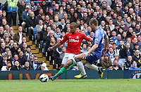 Pictured: Wayne Routledge gets a cross in for Swansea challenged by Gary Cahill<br /> Barclays Premier League, Chelsea FC (blue) V Swansea City,<br /> 28/04/13