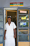A health official at the Bukavu Barracks public clinic in Kano Nigeria stands next to a Waterguard advertisement.  Waterguard is a chlorine-based product that makes water safe to drink.  It is distributed through social marketing by the Society for Family Health (SFH), the largest indigenous NGO in Nigeria.  SFH partners with the US-based international NGO, Population Services Intrenational.  This clinic also dispenses SFH injectable contraceptives oral contraceptives condoms and long lasting insecticide treated mosquito nets.