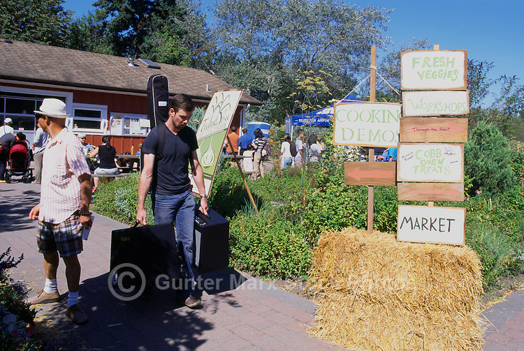 5th Annual Garlic Festival, August 2013 (hosted by The Sharing Farm) at Terra Nova Rural Park, Richmond, BC, British Columbia, Canada - Musician Performer walks past Directions to the Festivities