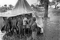 Uganda. West Nile. Adjumani. Ogujebe is distant 15 km from Adjumani and is a transit camp for refugees from South Sudan. A group of young boys stand under a tent during a heavy rain storm. West Nile sub-region (previously known as West Nile Province and West Nile District) is a region in north-western Uganda. © 1989 Didier Ruef