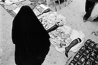 Iraq. Kerbala. The town of Kerbala is a holy place because of two mosques distant 500 meters one from the other: Imam Abbas mosque  and Imam Hussein mosque. A woman, wearing a long black dress and her head and body covered with a veil, shops for stockings on the walking path between both mosques. © 2003 Didier Ruef