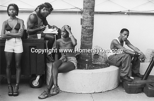 South Bech Miami Florida.  A group of young African American men and women absorbed in their own thoughts. 1990s USA