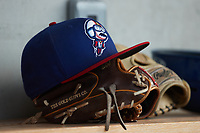 a Kannapolis Cannon Ballers cap sits on top of a Rawlings glove in the home dugout during the game against the Charleston RiverDogs at Atrium Health Ballpark on June 30, 2021 in Kannapolis, North Carolina. (Brian Westerholt/Four Seam Images)