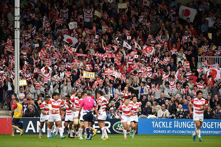 Japan supporters in the crowd celebrate a try. Rugby World Cup Pool B match between Scotland and Japan on September 23, 2015 at Kingsholm Stadium in Gloucester, England. Photo by: Patrick Khachfe / Stewart Communications