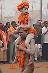 A young boy gets a ride in the parade of Naga sadhus