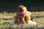 A smiling girl holding a daisy flower