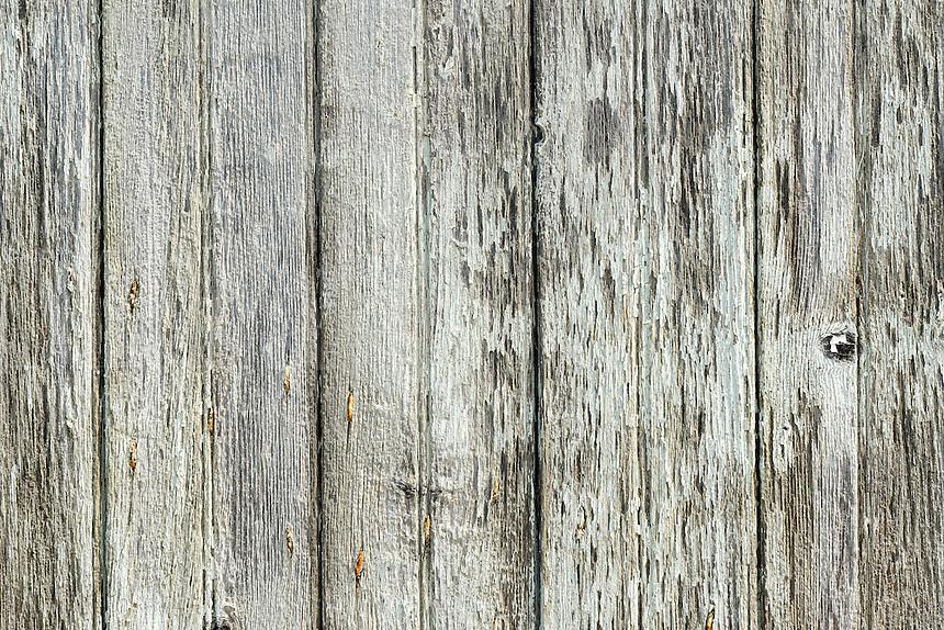 Detail of peeling paint on wood building.