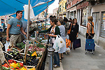 Venice Italy 2009. People doing vegetable shopping on canal boat Arsenale Venice.