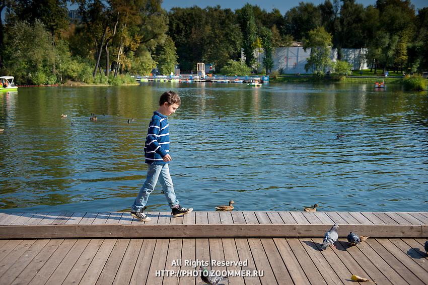 Boy walking on boardwalk near pond in Gorky park, Moscow, Russia