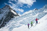 Three women ski touring on the Turtmanngletscher beneath a serac fall while on the way to the Tracuit Hut, Switzerland.